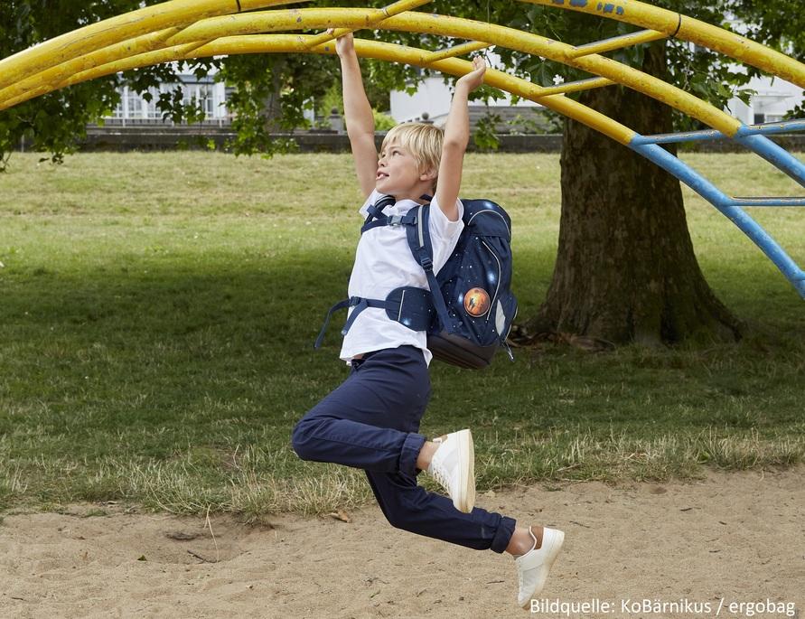 Junge turnt mit Rucksack
