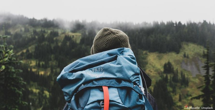 Mann mit Rucksack vor Wald
